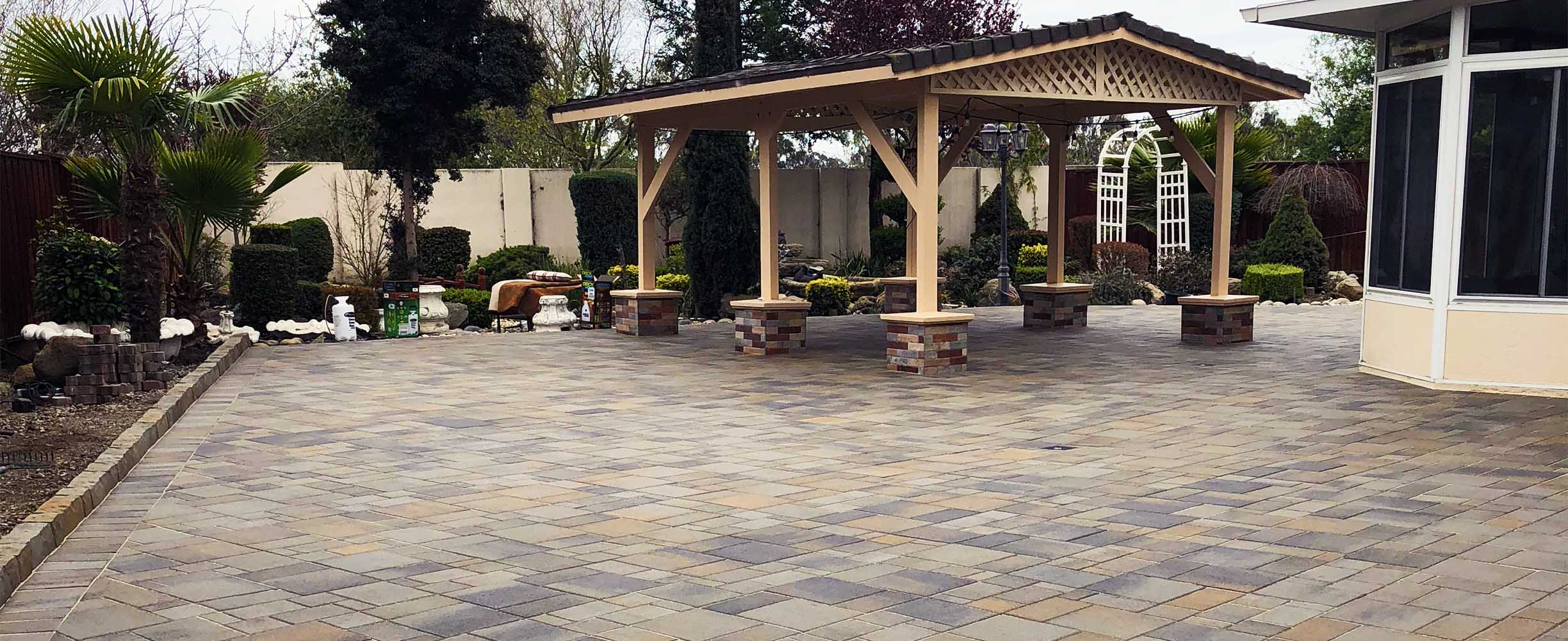 Landscaping projet of a pergola style wooden structure in a patio covered with stone pavers,antique style, in woodside, california.